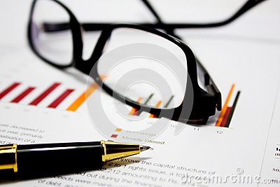 Business charts with glasses and pen