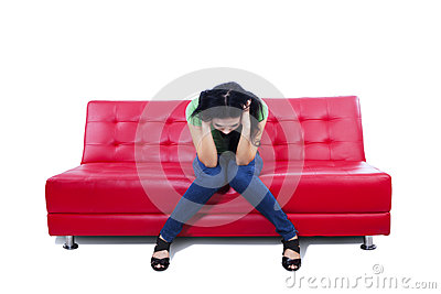 An image of depressed female on red sofa - isolated