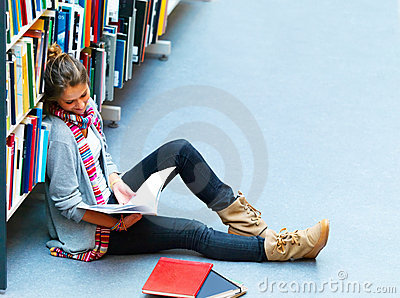 Image of a female student sitting by bookshelf