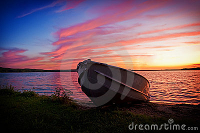 Image of fishing boat on shore of lake at sunset