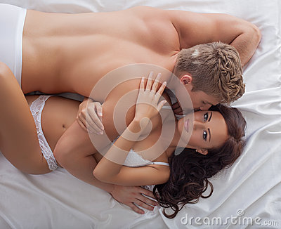 Image of passionate lovers hugging in bed