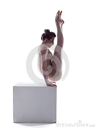 Image of slim acrobat doing exercises on cube