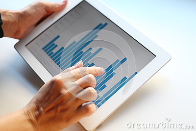 Image of woman hand pointing at touchscreen with business graph
