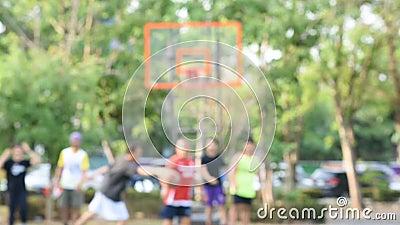 Imagen borrosa de los hombres, de las adolescencias mayores y de las mujeres jugando a baloncesto por la mañana en el parque de B metrajes