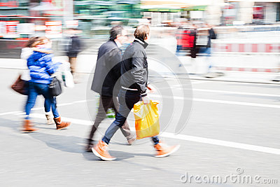 Gente de las compras que cruza la calle