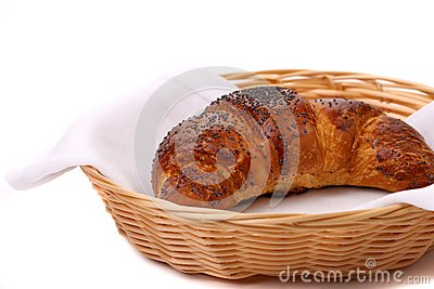 Imagen del cruasán con la amapola en una cesta.