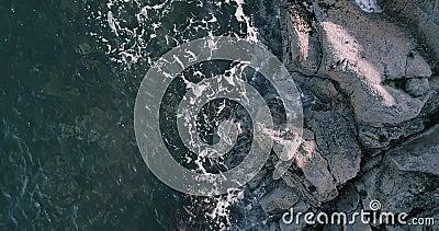 Impresionante vista aérea en cámara lenta del océano azul y olas estrellándose contra acantilados rocosos con chispas y espuma bl almacen de metraje de vídeo