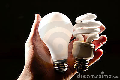 Incandescent and cfl lightbulb in human hand.