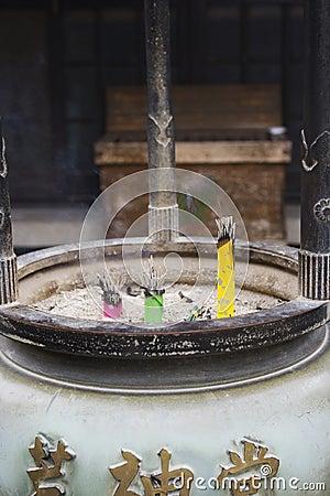 Incense sticks in pot near temple