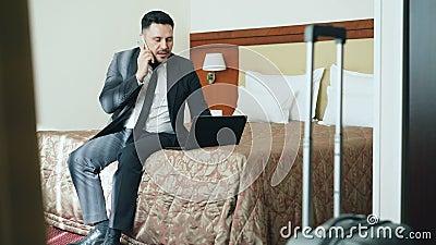 Incline acima do homem de negócios ocupado no terno que trabalha no portátil e que fala no telefone celular ao sentar-se na cama  filme