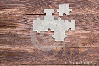 Incomplete wooden puzzles on brown wooden desk, top view, flat lay Stock Photo