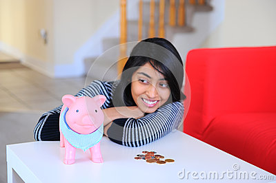 Indian beautiful girl looking to her piggybank