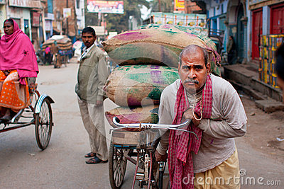 Indian loader works hard and carries bags of cargo on an old bicycle Editorial Photo