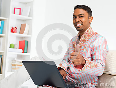 Indian man using computer at home.
