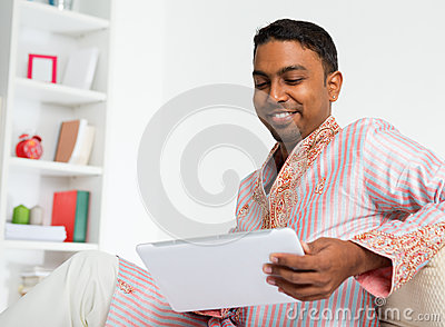Indian man using digital tablet at home.