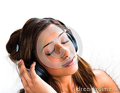 Indian teenage girl, with headphones, eyes closed