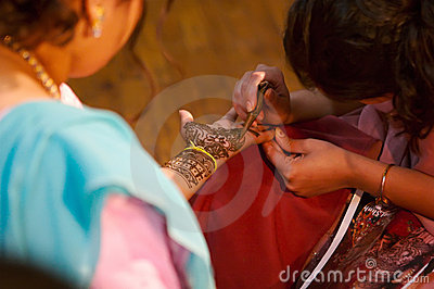 Indian wedding bride getting henna applied