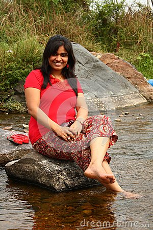 Indian woman in red dress sitting on a rock