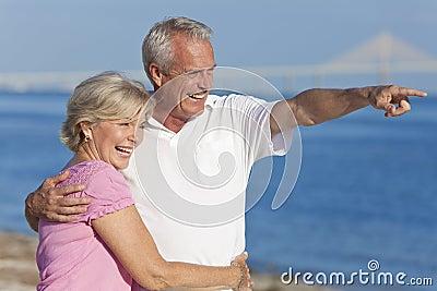Indicare ambulante delle coppie maggiori felici sulla spiaggia