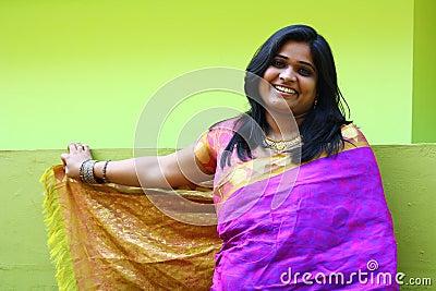 Indische Frau in der purpurroter Sareestellung und -c$lächeln