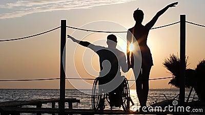 Indivíduo com pés doentes na cadeira de rodas com a amiga na viagem romântica contra o contexto do por do sol em feixes brilhante video estoque