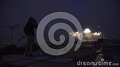 Indivíduo que está no telhado da construção alta que toma a foto dos fogos-de-artifício na câmera filme