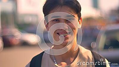 Individuo asiático feliz que se ríe de la cámara, primer que se coloca en la calle, coches y camino en el fondo, vida de ciudad almacen de metraje de vídeo