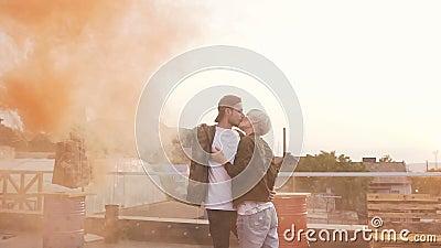 Individuo hermoso del inconformista que besa a su novia feliz romantically Hombre joven hermoso que celebra humo coloreado y beso almacen de metraje de vídeo