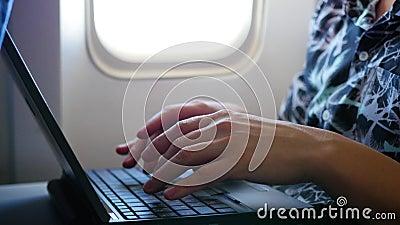 Individuo que trabaja en el ordenador portátil en el aeroplano cerca de la ventana almacen de metraje de vídeo