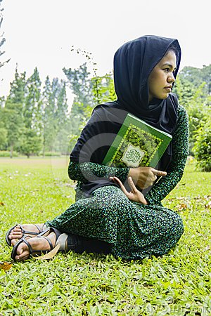 Indonesian moslim girl with a quran