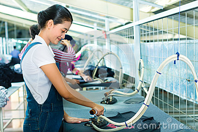 Indonesian worker with flat iron in textile factory