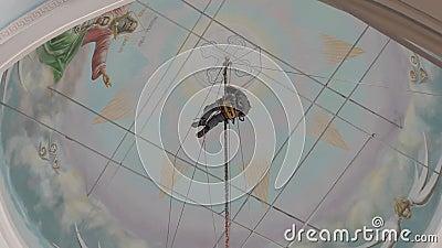 Industriële klimmer in apparatuur voor hoogstandwerk op grote hoogte in een kerkgebouw over de klimmer stock video