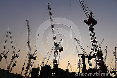 Industrial crane at construction site during sunset.