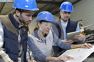Industrial engineers meeting and discussing in mechanical factory Stock Photo