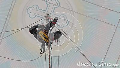Industriell klättrare i utrustning för arbete på hög höjd i en kyrkobyggnad på stigarna arkivfilmer