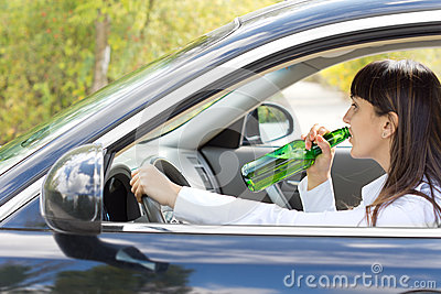 Inebriated female driver drinking alcohol