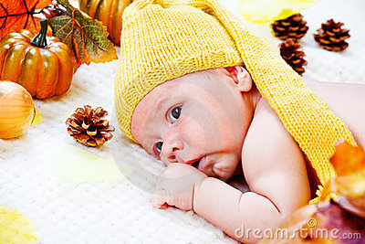 Infant  among autumnal leaves and pumpkins