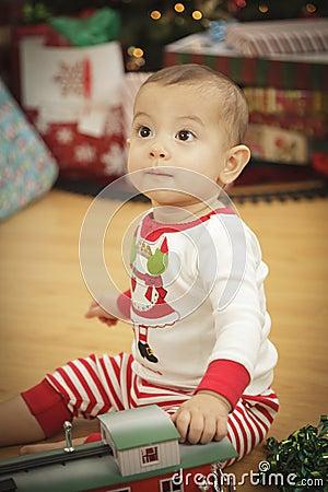 Infant Baby Enjoying Christmas Morning Near The Tree
