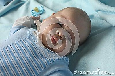 Infant boy refusing a dummy