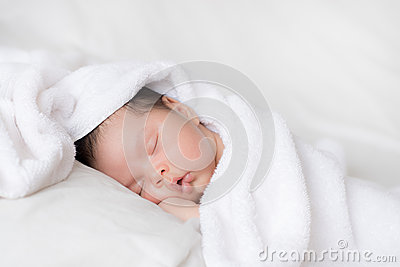 Infant boy sleeping on white bed