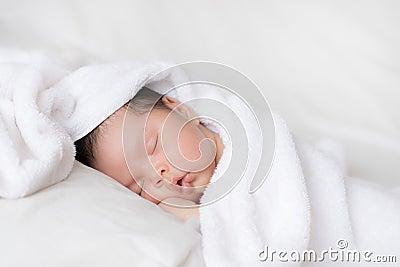 Infant boy sleeping on white bed