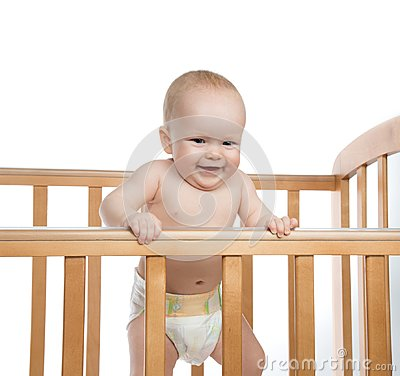 Free Infant Child Baby Girl In Wooden Bed Looking Down Happy Smiling Stock Photography - 106700232