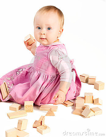 Infant girl playing with wooden blocks