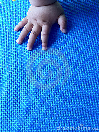 Infant hand on the mat