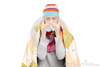 Infected woman covered with blanket blowing her nose in tissue