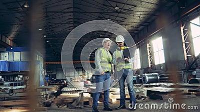 Ingénieurs professionnels de l'industrie lourde Deux ouvriers parlent dans une usine de matériaux de construction banque de vidéos