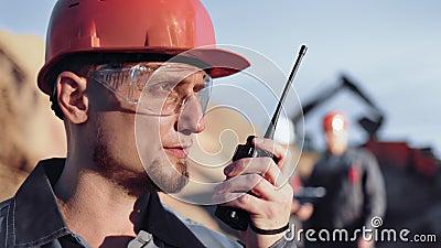 In ingegnere di costruzione maschio esperto in segnalazione dell'uniforme facendo uso del walkie-talkie durante il primo piano di video d archivio