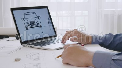 Ingeniero que trabaja en un bosquejo del diseño del coche usando su ordenador portátil almacen de metraje de vídeo