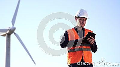 Ingenieur des kaukasischen Auftrittes in einem Sturzhelm und Weste schauen die Arbeit der Windmühle und betrachten die Tablette stock video
