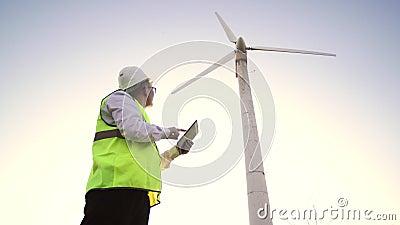 Ingenieur für asiatisches Aussehen konfiguriert den Betrieb der Windmühle mit seiner Tablette in der Hand stock video footage